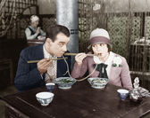 Couple sharing a noodle in a restaurant — Stockfoto