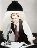 Uomo appoggiato sopra una scrivania con una lampada da soffitto splendente su di lui — Foto Stock