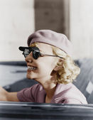 Young woman with a beret and sunglasses in a car, on the go — Stock Photo