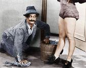 Adam bir kadının bacaklarına bakarak zemin temizleme — Stok fotoğraf