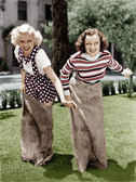 Two women playing a game of potato sack racing — Stock Photo