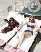 Chimpanzee and a woman sunbathing — Stock Photo