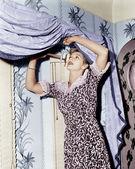 Woman hanging a valance — Stock Photo