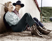 Laughing couple in western attire sitting on the ground — Stock Photo