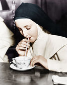 ストローで茶碗のお茶をすすりながら修道女 — ストック写真