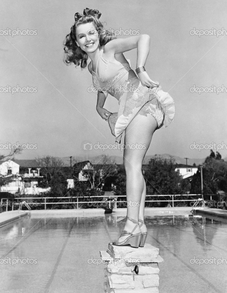 Woman posing on top of a pillar next to a swimming pool — Stock Photo #12300313
