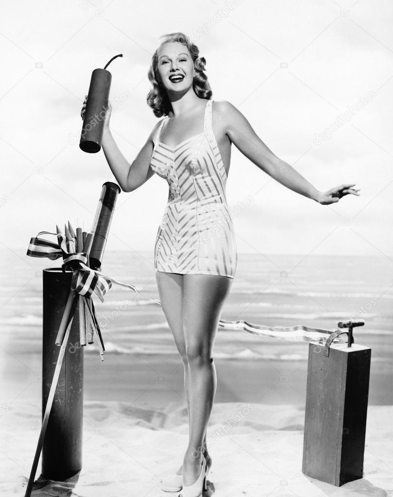 Woman in a bathing suit at the beach holding an oversized fire cracker in her hands — Stock Photo #12300355