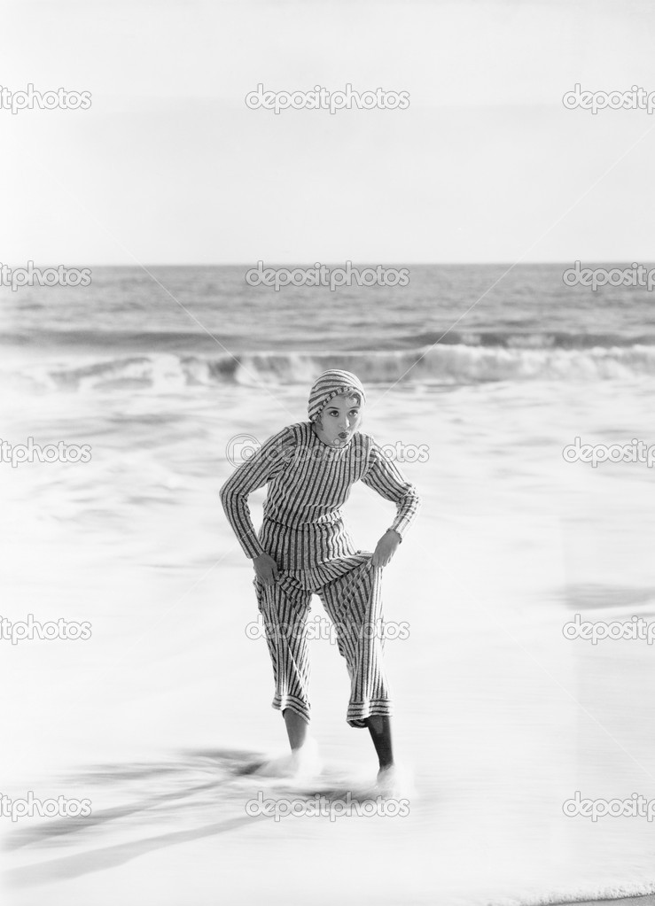 Woman in a striped suit stepping out of the ocean — Stok fotoğraf #12300518