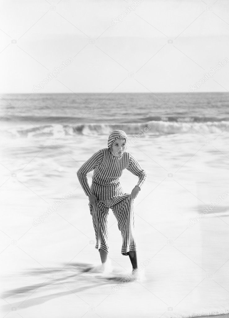 Woman in a striped suit stepping out of the ocean — Zdjęcie stockowe #12300518
