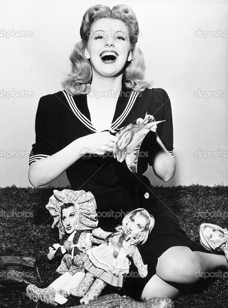 Woman laughing and cutting out paper dolls faces — Stock Photo #12300536