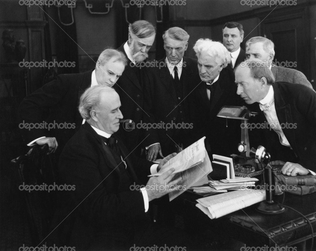 Men hovering around desk in anticipation of news — Foto Stock #12301642