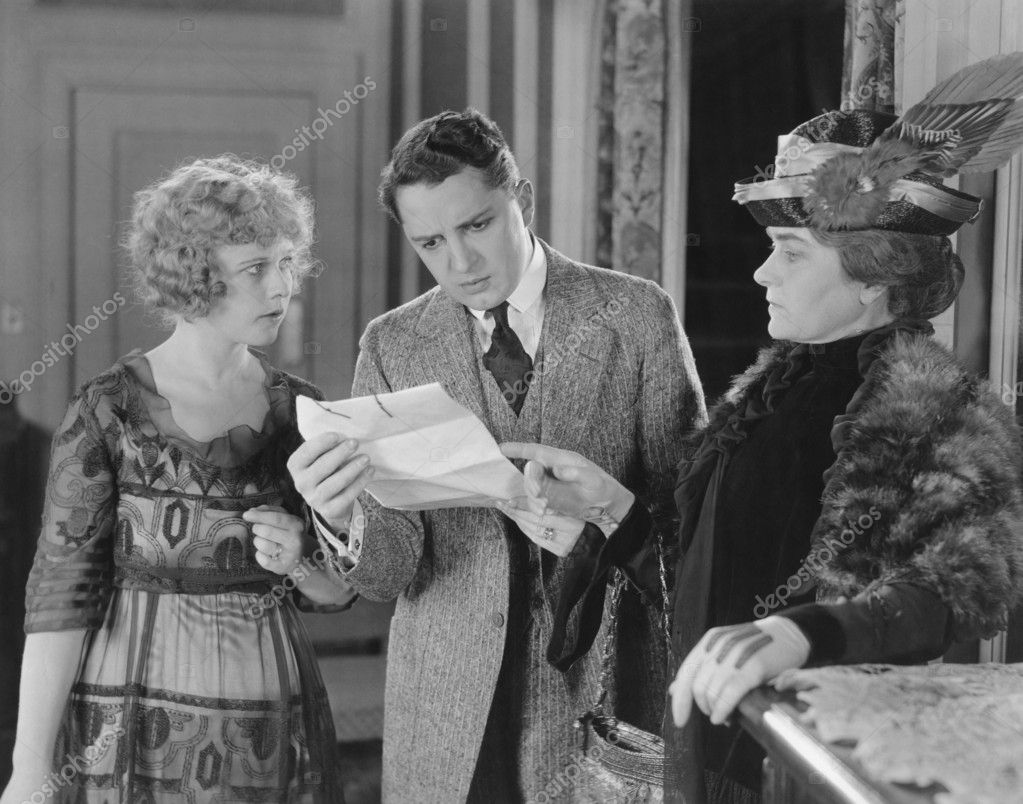 Man reading letter with two women looking over his shoulder  Stock Photo #12301706