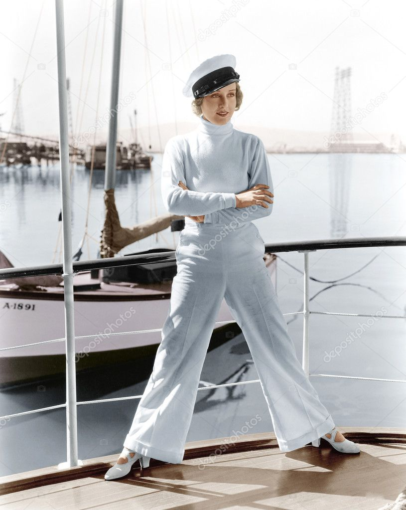 Woman in a captains hat standing on top of a sailboat — Foto Stock #12302771