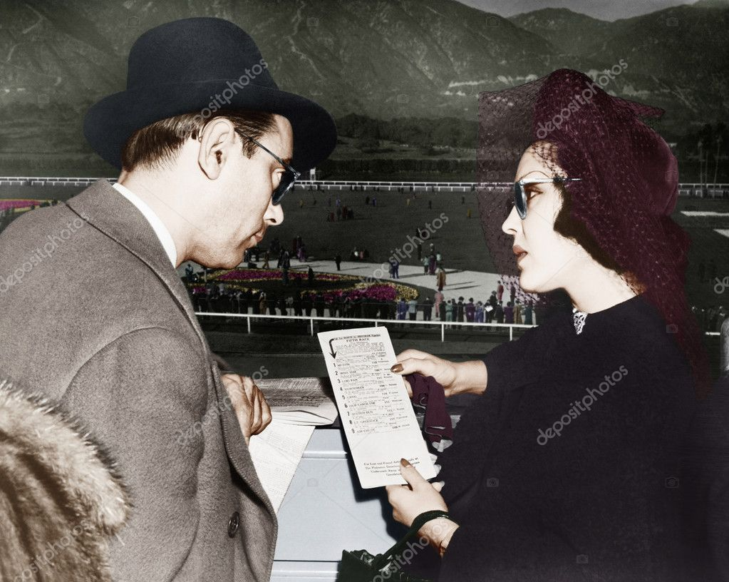 Elegant couple at a horse race looking at a program — Stock fotografie #12303001