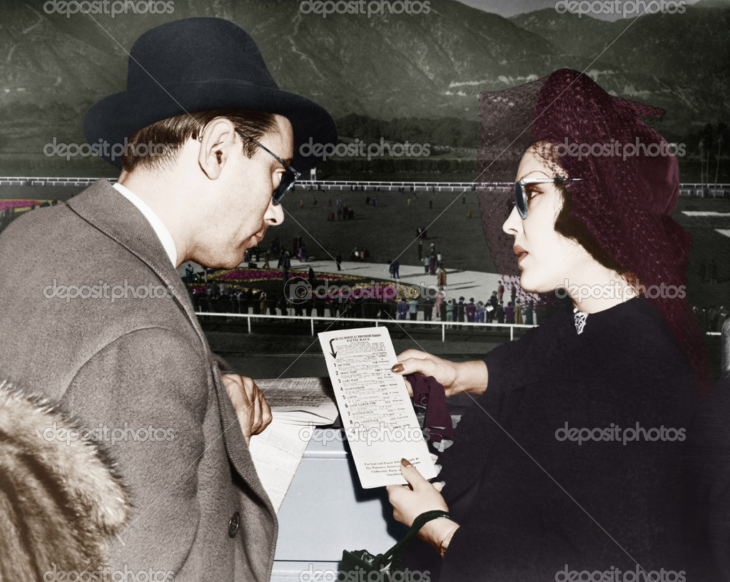 Elegant couple at a horse race looking at a program — Stok fotoğraf #12303001