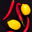 Wet lemons and peppers — Stock Photo #12211874
