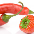 Hot pepper stems and strawberry on white surface — Stock Photo