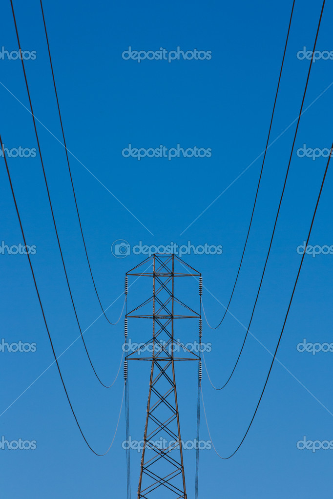 Power transmission lines hang from a steel lattice tower against a blue sky background. — Stock Photo #12304489