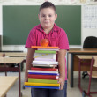 Boy with stack of books in the classroom — Stock Photo