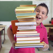Stock Photo: Happy boy with stack of books in a classroom