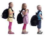 Childeren in a row with backpacks — Stock Photo