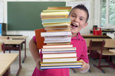 Happy boy with stack of books in a classroom — Stock Photo