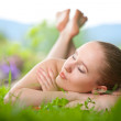 Young woman lying in a grass — Stock Photo