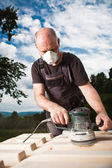 Carpenter sanding a wood with sander — Stock Photo