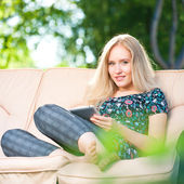 Positive beautiful young woman sitting outdoors in armchair seat — Stock Photo