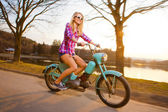 Young beautiful woman riding a lifestyle vintage bike during sun — Stock Photo