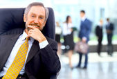 úspěšný obchodní muž stojící s jeho zaměstnanci v pozadí v kanceláři