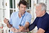Dottore prendendo la pressione sanguigna di un paziente
