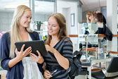 Zákazník s kadeřnicí drží digitální tabletu