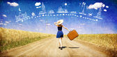 Osamělá dívka s kufrem na zemi silnici snil o cestování