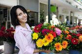 žena s velkou kytici květin venku