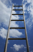 Ladder reaching into a blue sky