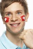 Mladý samec sportovní fanoušky švýcarské vlajky na obličej