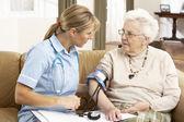 Starší žena ihaving krevní tlak přijatá ošetřovatelkou v h