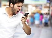 Portrét angry young man výkřiky pomocí mobilní na přeplněném m