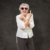 Senior woman wearing sunglasses doing funky action