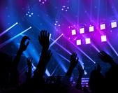 Sfondo, luce colorata astratta, confine di sagoma di mani umane, felice salto grande gruppo festeggia Capodanno vacanze, godendo la musica della band dal vivo in night club di uomini di partito, il concetto di divertimento