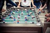 Consiglio di calcio allaperto tavolo verde con molte figure colorate e un paio di giocatori intorno