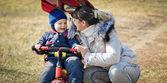 Matka pomáhá batole jízda tříkolka