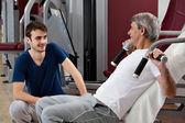 Gym training, young man and his father