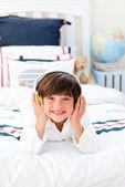Veselá malý chlapec poslech hudby se sluchátky na