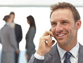 Happy businessman on the phone during a meeting