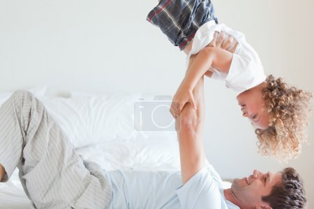 床上提升孩子的父亲的侧视图