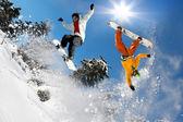 Snowboardista skákání proti modré obloze