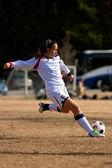 Un giocatore di calcio del liceo femminile oscilla indietro la gamba e si prepara a calciare la palla durante una partita