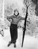 Woman standing in the snow with her skies in hand
